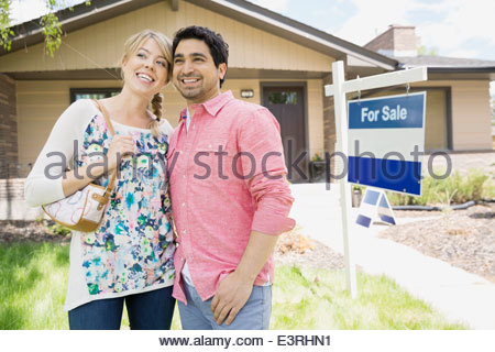 Couple smiling suivant pour For Sale sign Banque D'Images