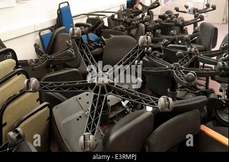 Nouvelle construction ou la fermeture de bureaux ordinateur chaises empilées entassées chaotiquement en salle vide Banque D'Images