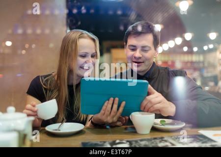 Les jeunes à boire du café et à la recherche sur les surfaces Banque D'Images