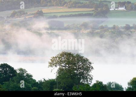 Lochwinnoch, Renfrewshire, Écosse, Royaume-Uni, lundi 30 juin 2014. Brume se formant au lever du soleil au-dessus du Loch du Château Semple au début d'une journée qui devrait être sèche, chaude et ensoleillée