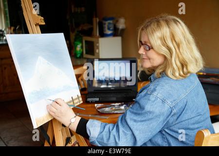 Peinture femme dans la cuisine à l'aide de photographie sur l'écran de l'ordinateur comme référence Banque D'Images