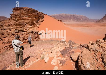 La Jordanie, Wadi Rum, touristes occidentaux affichage des dunes de sable rouge de l'éperon rocheux Banque D'Images