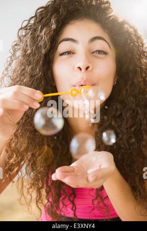 Mixed Race woman blowing bubbles Banque D'Images