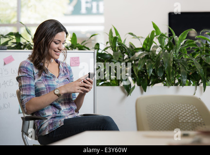Ambiance young businesswoman texting on smartphone in office Banque D'Images