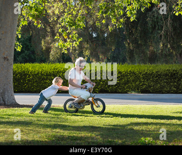 Trois ans grand-mère poussant sur cycle in park Banque D'Images