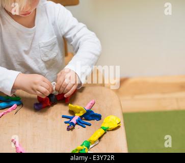 Cropped shot de trois ans jouant avec de la pâte à modeler Banque D'Images
