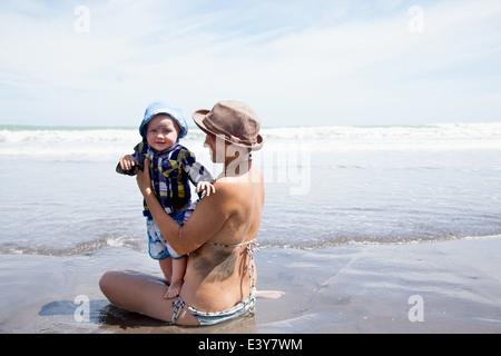 Jeune femme assise dans la mer avec son bébé Banque D'Images