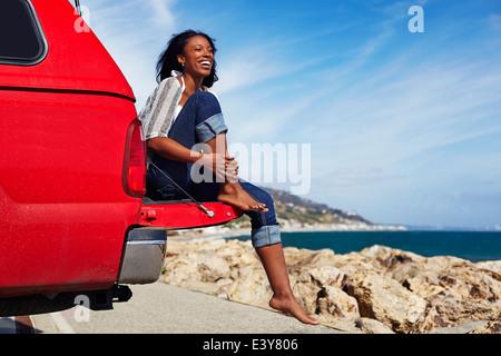 Jeune femme assise sur un capot de voiture, Malibu, California, USA Banque D'Images