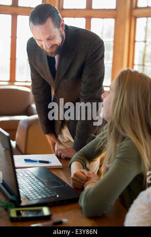 Young woman with laptop parler à l'enseignant Banque D'Images