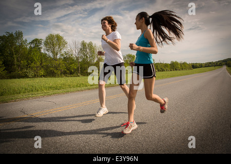 Mid adult woman and young woman running on road Banque D'Images