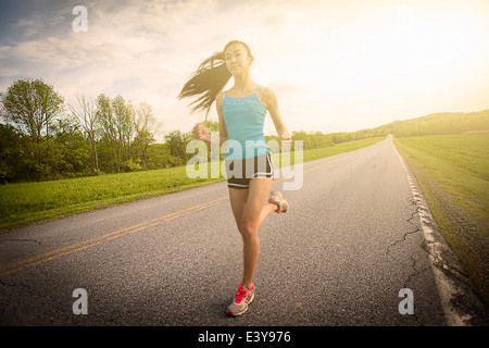 Teenage girl running on road Banque D'Images