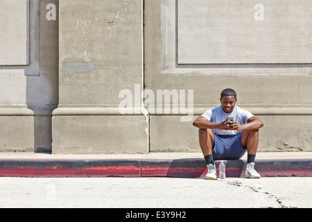 Young male runner assis sur trottoir texting on smartphone Banque D'Images