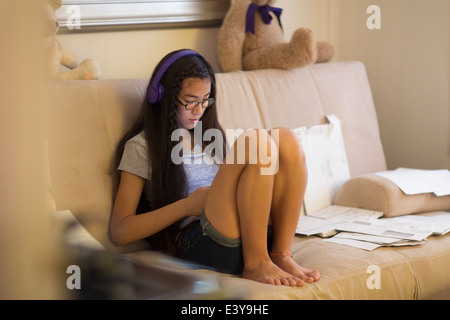 Teenage girl sitting on sofa, portant des écouteurs Banque D'Images
