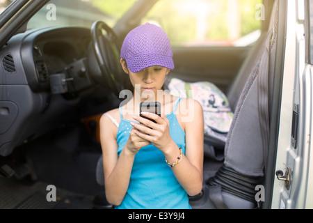 Teenage girl debout à côté de voiture ouverte, à l'aide de mobile phone Banque D'Images