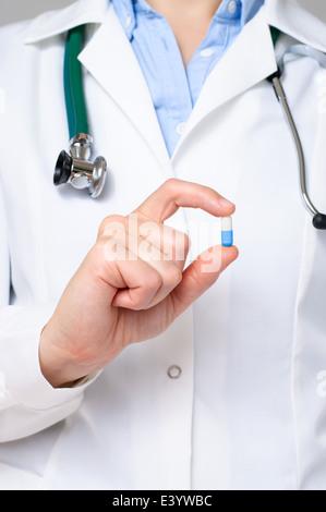Médecin montrant une pilule bleue