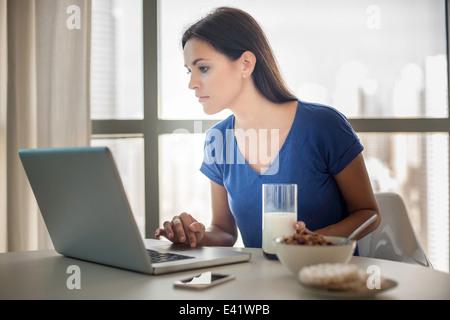 Young woman using laptop tout en ayant le petit déjeuner Banque D'Images