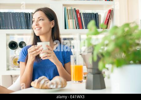 Jeune femme ayant le petit déjeuner Banque D'Images