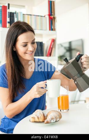 Young woman pouring coffee pour le petit déjeuner Banque D'Images