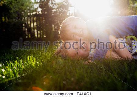 Frère et sœur couchée sur l'herbe, serrant Banque D'Images