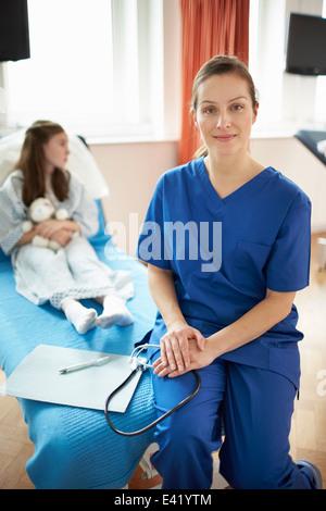 Nurse sitting on fin de lit du patient Banque D'Images