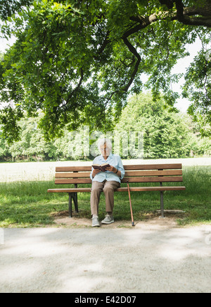 Senior woman sitting on park bench reading bible Banque D'Images