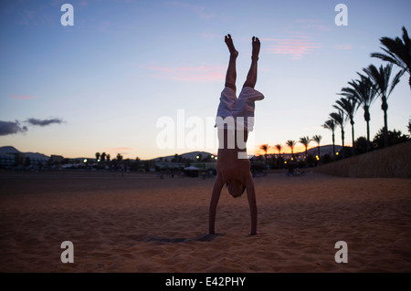 Silhouetté boy doing handstand on beach at Dusk Banque D'Images