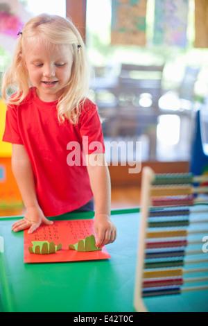 Girl comptage avec les doigts à l'école maternelle Banque D'Images
