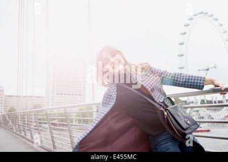 Portrait of young woman swinging sur Golden Jubilee passerelle, London, UK Banque D'Images