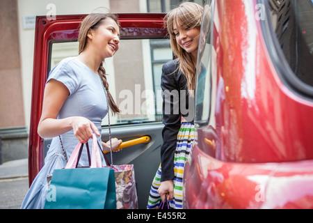 Les jeunes femmes d'entrer dans taxi, carrying shopping bags Banque D'Images