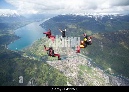 Équipe de quatre parachutistes en formation au-dessus d'Interlaken, Berne, Suisse Banque D'Images
