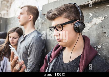 Adolescent avec des écouteurs, les amis en arrière-plan Banque D'Images