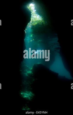 La lumière dans une grotte peu profonde en continu dans un site appelé Le Passage, avec un plongeur nageant à travers. Banque D'Images