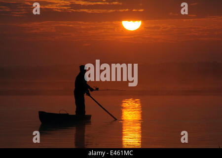 La silhouette du pêcheur La pêche à la ligne du traditionnel punt comme le soleil se lève sur la rivière Biebrza Banque D'Images