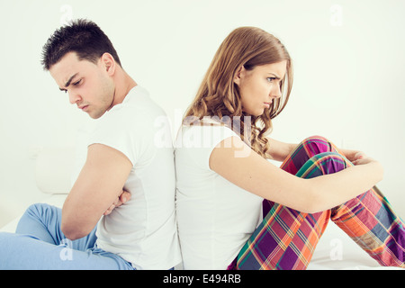 Jeune couple ayant bouleversé les problèmes conjugaux ou un désaccord assis côte à côte dans le lit dos à dos et Banque D'Images