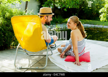 Couple hétérosexuel prend une pause par l'étang, Munich, Bavière, Allemagne Banque D'Images