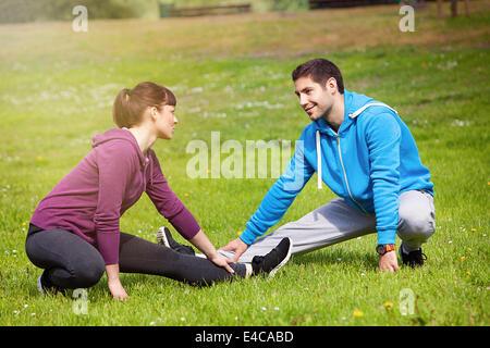 Jeune couple stretching en parc, Osijek, Croatie Banque D'Images