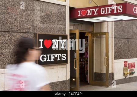 Une femme marche d'un magasin de cadeaux I Love NY en New York, NY Banque D'Images