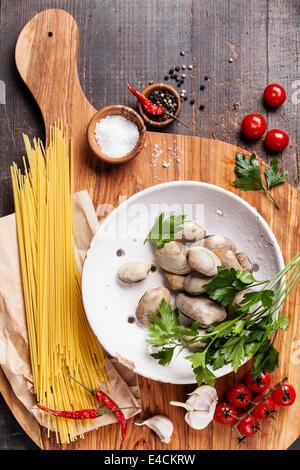 Ingrédients pour la cuisson des coquilles vongole spaghetti vongole, matières sapaghetti, les feuilles de persil, Banque D'Images