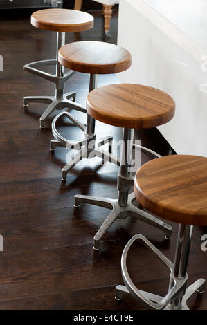 Ensemble de quatre tabourets de bar chromé avec sièges en bois Banque D'Images
