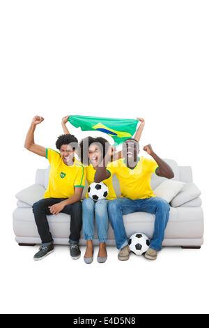 Les fans de football brésilien en acclamant jaune sur le canapé Banque D'Images