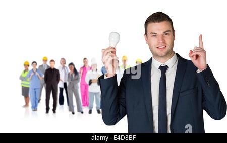 Composite image of businessman holding Light bulb et vers