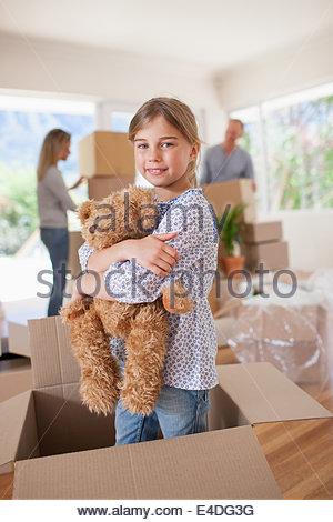 Fille jouant avec ours en peluche dans la case in new house Banque D'Images