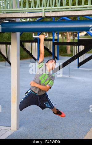 Garçon jouant sur l'aire de jeux au parc au bord de l'eau à Louisville Kentucky Banque D'Images