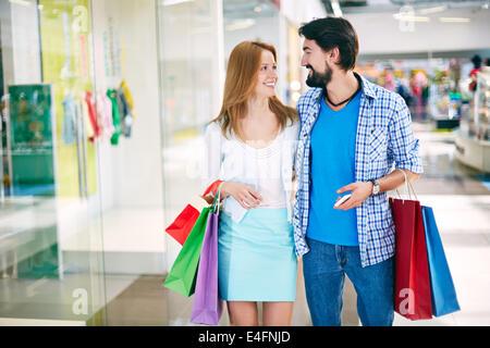 Portrait of happy young couple interagir tout en faisant du shopping dans le centre commercial Banque D'Images