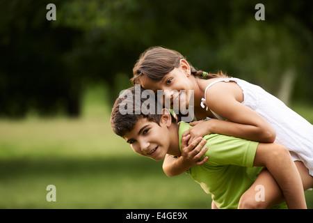Les gens dans l'amour avec happy little girl and boy running s'y greffent en parc de ville. Copy space Banque D'Images