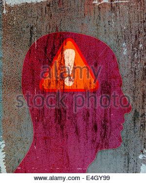 Panneau d'avertissement d'exclamation à l'intérieur de la silhouette de tête de l'homme Banque D'Images