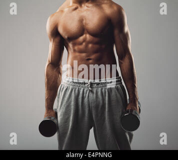 Portrait d'homme fitness model holding haltères en deux mains sur fond gris. Jeune homme musclé l'élaboration avec Banque D'Images