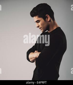 Vue latérale du jeune homme debout avec les bras croisés à la recherche vers le bas. Modèle masculin hispanique sur fond gris.