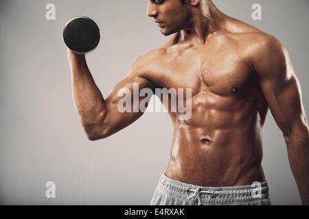 Portrait de jeune homme musclé accomplir un exercice d'haltères pour biceps. Man working out with dumbbells sur Banque D'Images