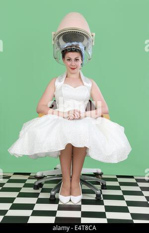 Femme en robe de mariage style années 50, assis sous un sèche-cheveux salon vintage Banque D'Images